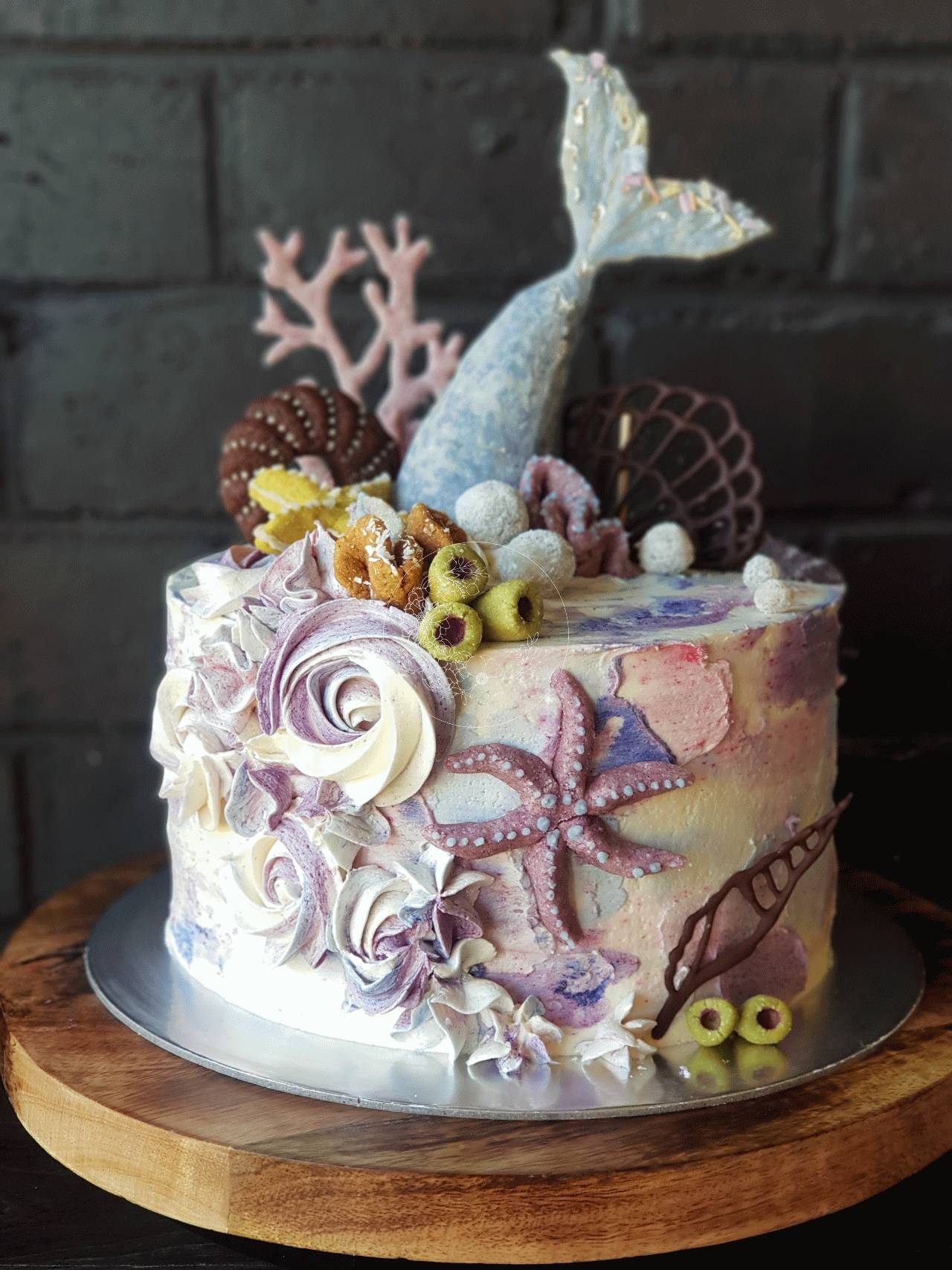 Mermaid Theme cake, the mermaid tail and coral was made using coconut bliss ball receipe, textured icing and swirls of icing, coconut sugar cookie sea animals and chocolate shells