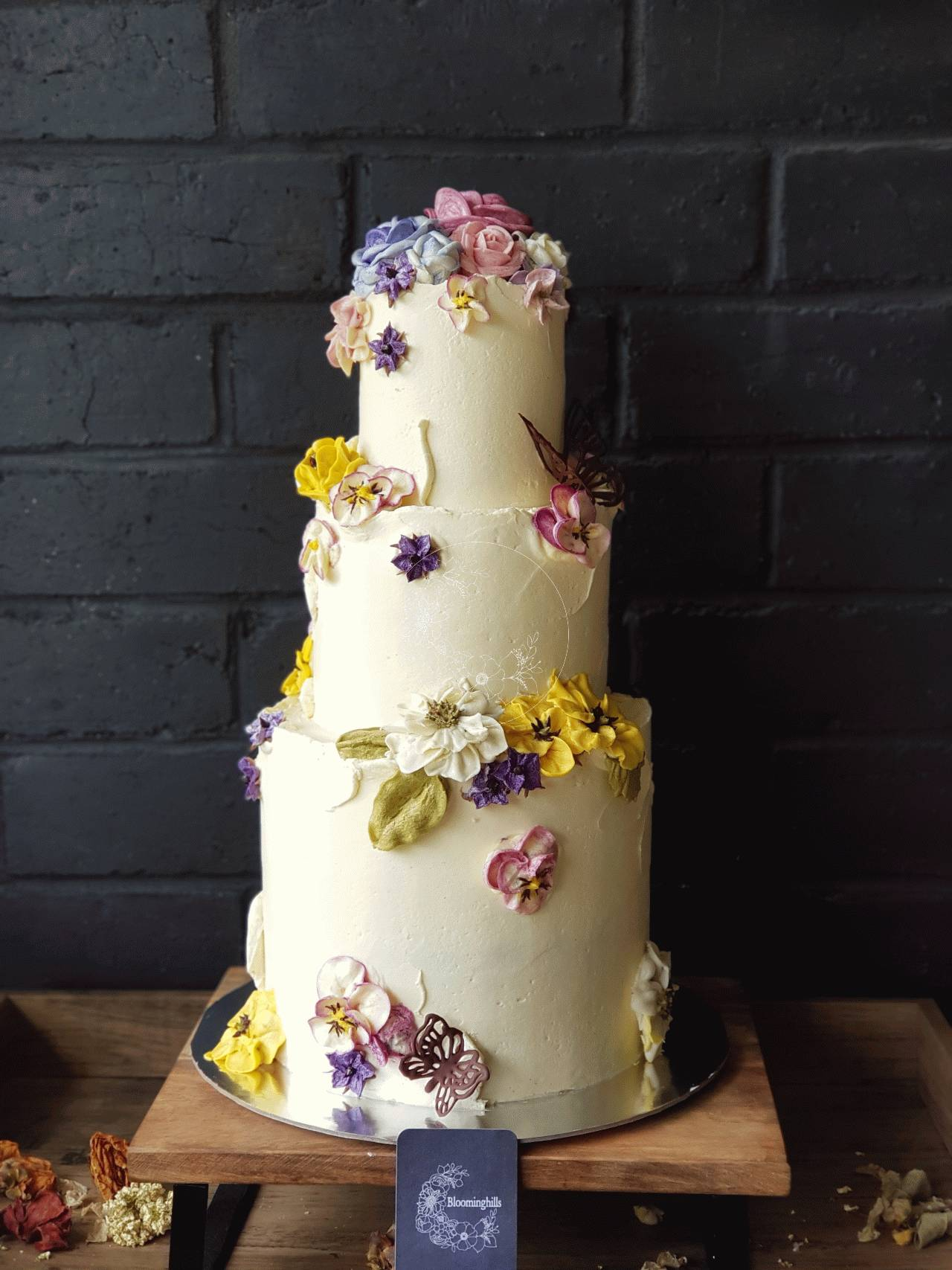 Sweet Blossom 3 Tier Wedding cake - Extended height bottom tier with flowers to match a small cottage garden with roses, pansies and other blossoms and chocolate butterflies