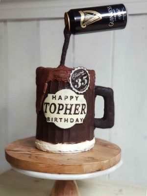 Something unique Gravity Defying beer cake, with doughnuts, custom chocolate topper and chocolate ganache icing