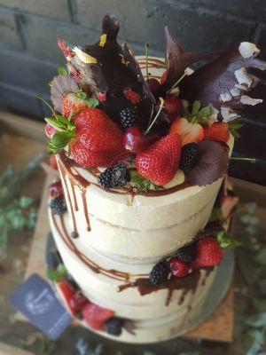 Indulgence Wedding cake - Two tier, extended height cake with semi naked icing, fresh fruit, chocolate garnishes, and salted caramel drip