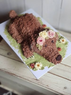 Designed to look like their dog, Coco. This 3D cake is decorated with buttercream fur and flowers