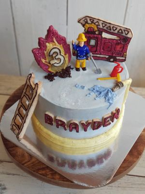 Fireman Sam Theme cake with figurine. Something Unique with vanilla buttercream hose, cookie fire truck, ladder and flames. figurine dipped in agar jelly to provide clean surface