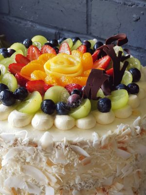 Fruit Flan Cake - Vanilla cake base with vanilla buttercream, coconut flakes, custom chocolate topper, fresh fruit and chocolate garnish on top