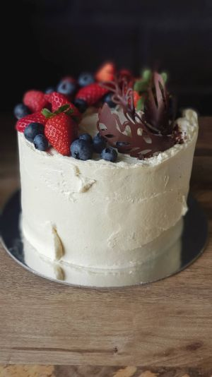 Indulgence cake, textured icing, topped with fruit and chocolate garnishes