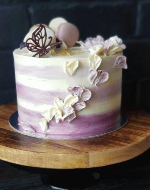 Indulgence cake, with vegan macarons, blueberries, chocolate garnish buttercream petals and three shade pink icing.