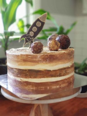 Jupiter cake, designed for a 21st birthday, featuring textured coloured icing, and cake pop moons made to scale resembling NASA photos of the moons