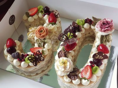 Number 30 cake, with cake base, featuring buttercream flowers, chocolate garnish and fresh fruit