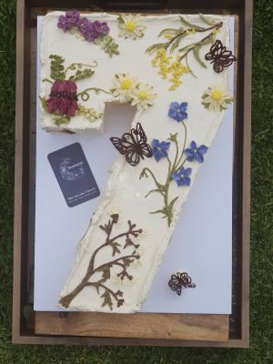 Sweet Blossom - Number 7 cake - Fully iced, textured finish topped with a selection of native flowers including, Wattle, Sturt Desert Pea, Daisies, Bluebells, and acacia blossoms with choc butterflies
