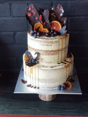 Vanilla Orange Tier Cake with chocolate, candied and fresh fruit garnishes, topped off with a salted caramel drip