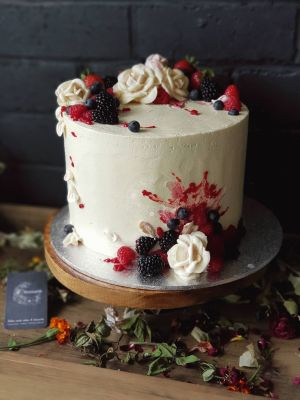 Indulgence Berry cake, textured icing with buttercream flowers and petals, compote splash and fresh berries.
