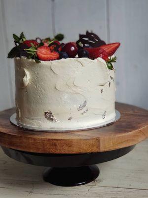 Indugence cake with textured icing, strawberries, cherries, blueberries and dark chocolate garnish