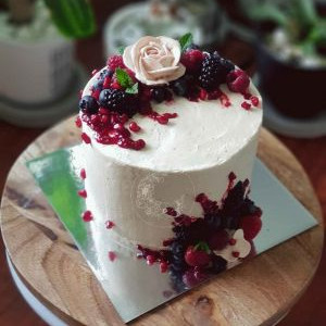 Indulgence cake, full vanilla icing, with fresh berries and pomegranate, and custom chocolate topper